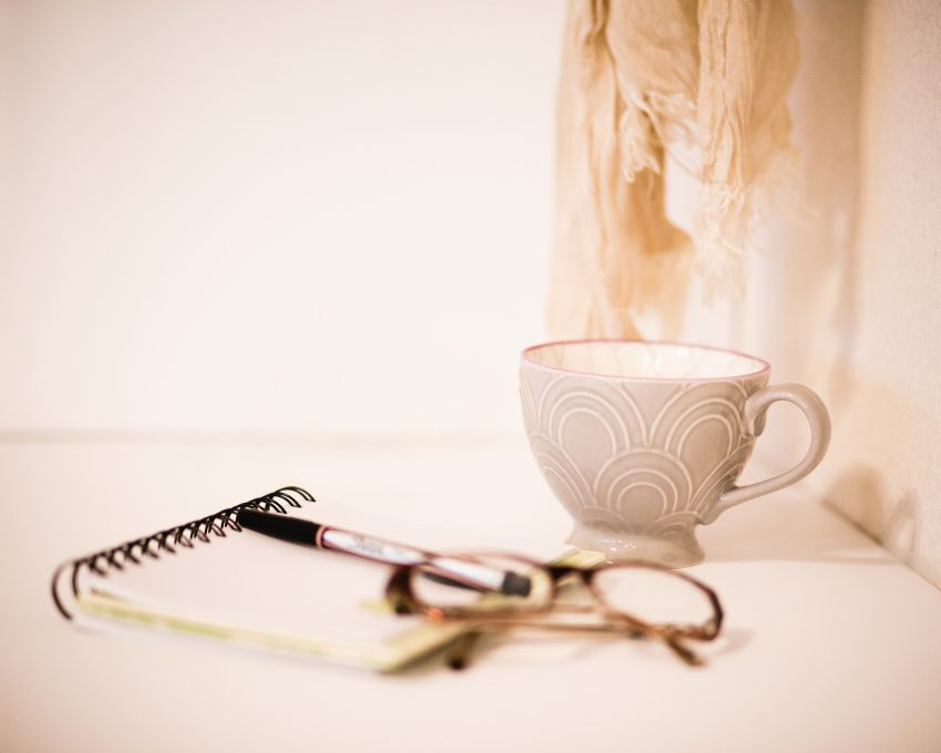 Teacup, notebook and reading glasses