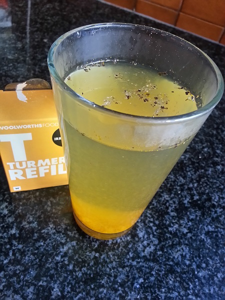 Warm turmeric drink with lemon juice and black pepper.