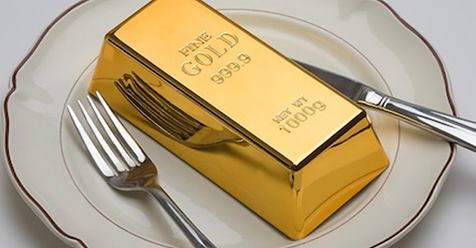 Gold bar on a plate with knife and fork